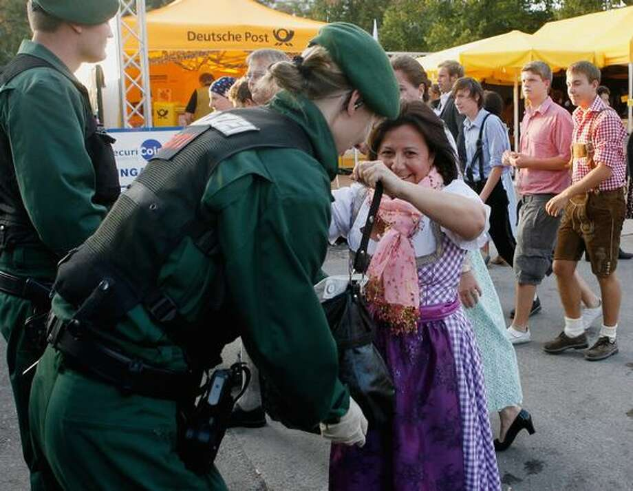 A female police officer checks the handbag of a woman wearing a traditional Bavarian Dirndl dress at the main entrance of the Oktoberfest beer festival in Munich on Monday in Munich, Germany. Germany is on a heightened security alert after receiving a terror threat video from what officials say is a German-speaking Al Qaeda operative. Photo: Getty Images / Getty Images