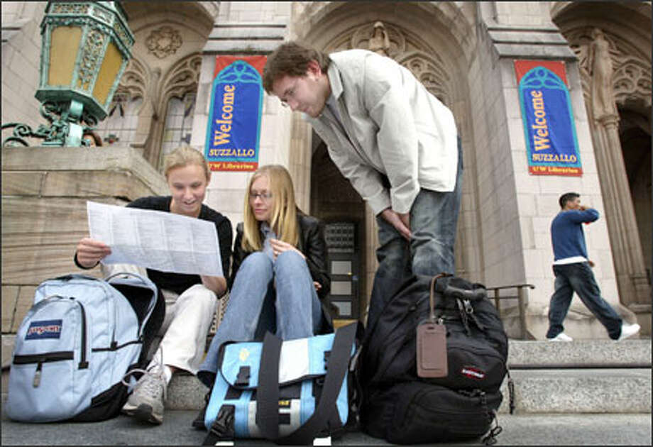 University of Washington graduate students, from left, Erin Vernon, Nina Sidneva and Francois Briand try to find the buildings where they will teach economics to undergraduates on the first day of school Tuesday. Photo: Joshua Trujillo, Seattlepi.com / seattlepi.com