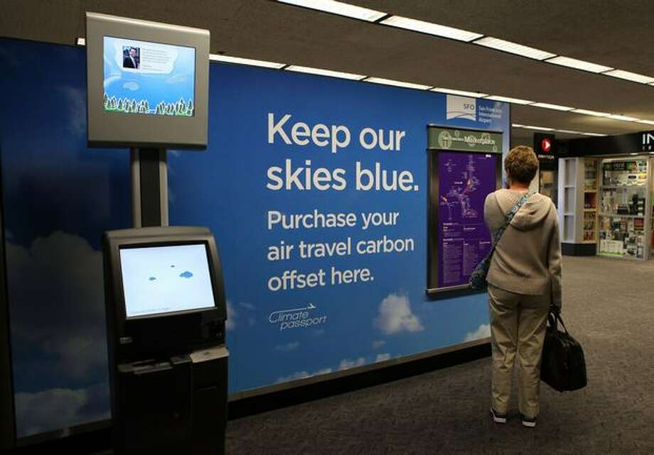 A traveler stands near a new Climate Passport carbon offset kiosk, Tuesday, at San Francisco International Airport in San Francisco, California. San Francisco International Airport became the first airport in the country to offer self-serve kiosks made by Climate Passport where carbon offsets, a financial instrument aimed at reducing greenhouse gas emissions, fcan be purchased by travelers for their flights. Photo: Getty Images / Getty Images