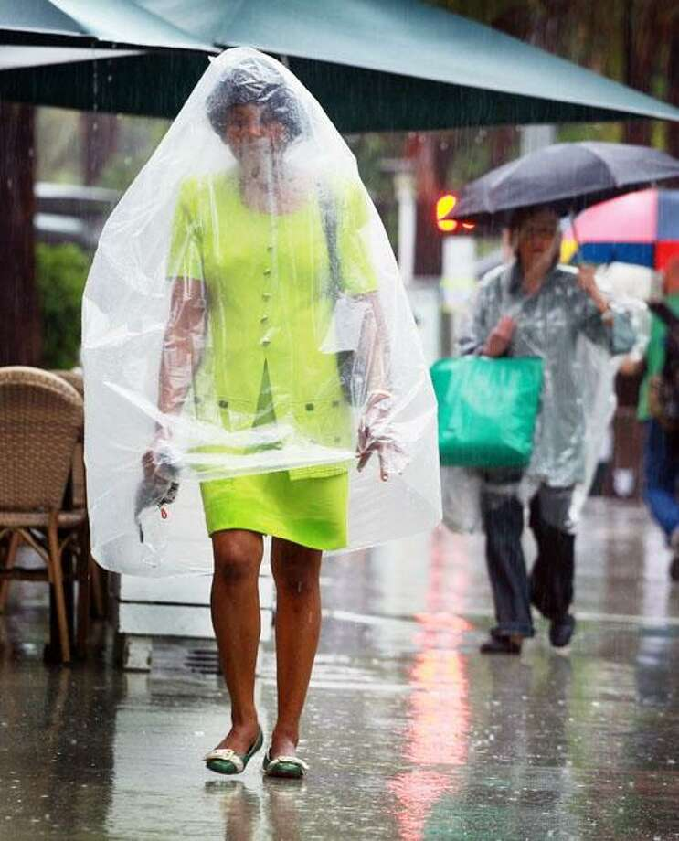 Recycle your dry-cleaning bag!Caught without a raincoat by the outer bands of Tropical Storm Nicole, a Miami Beach resident uses the next best thing to stay dry. Photo: Joe Raedle, Getty Images / Getty Images