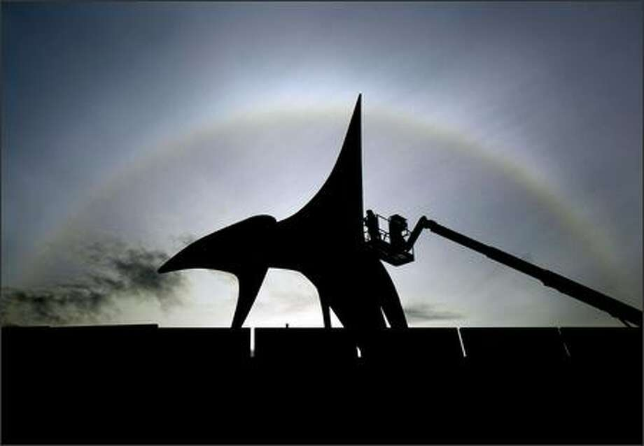 "A worker is silhouetted Monday while installing Alexander Calder's ""Eagle"" at SAM's Olympic Sculpture Park. Overhead, the sun creates a halo on high cirrus clouds. Photo: Joshua Trujillo, Seattlepi.com / seattlepi.com"