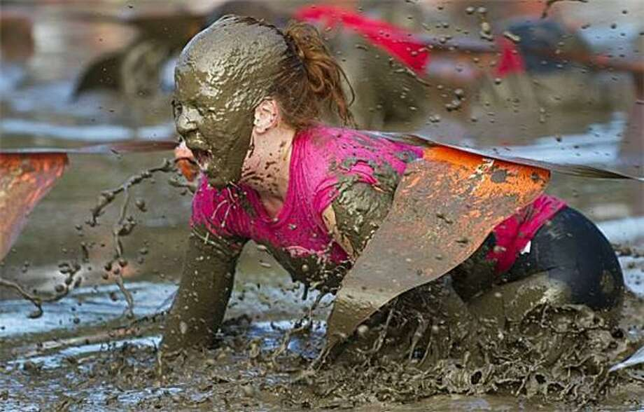 Here's mud in her eye: A competitor gets a face full of muck during the Merrell Down and Dirty Mud Run, a military-style obstacle-course race in Orchard Beach, N.Y. Thousands took part in the race, which included cross-country running, wading in ponds, crawling through mud and scaling a wall covered with soap. Photo: Don Emmert, AFP / Getty Images / AFP / Getty Images