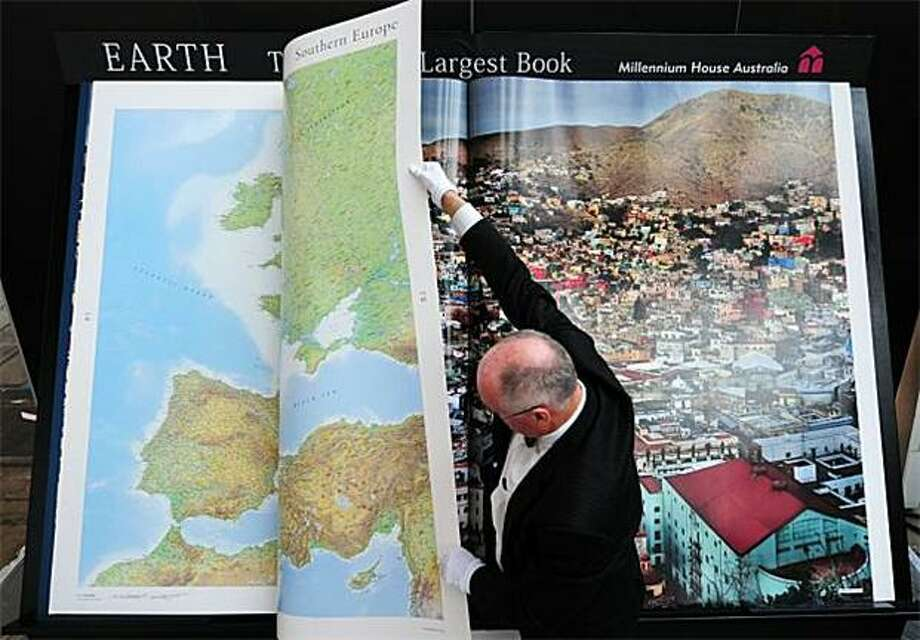 Tome dome: It takes two gloved hands to turn the pages of the so-called world's largest book at the 62nd Frankfurt Book Fair in Frankfurt am Main, Germany. The 6- by 9-foot atlas was printed by Australian publisher Gordon Cheers, who said that no book this size has been produced for 350 years. Photo: Johannes Eisele, AFP / Getty Images / AFP / Getty Images