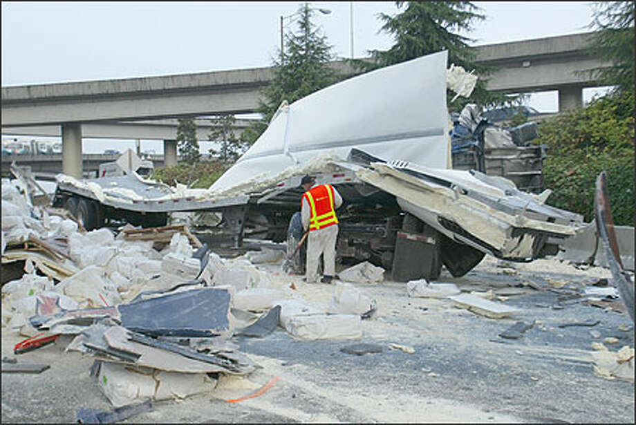 A semi-truck and trailer loaded with soy protein products rolled off onto the northbound Dearborn exit from I-5 after heading northbound to I-5 from I-90. Two men were injured and the off-ramp was blocked for hours. Photo: Phil H. Webber, Seattle Post-Intelligencer / Seattle Post-Intelligencer