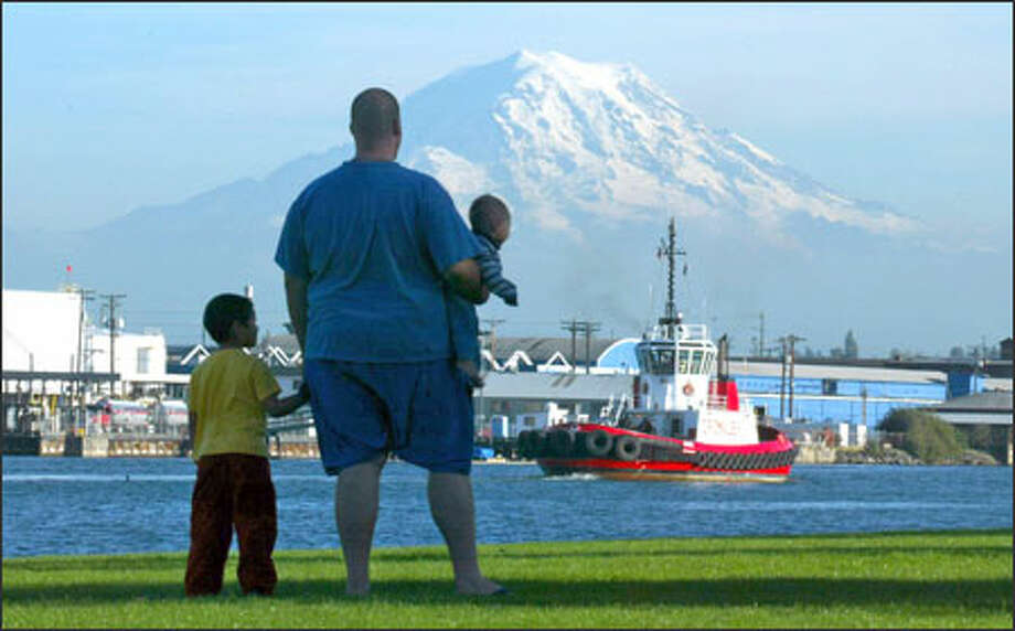 With Mount Rainier as a backdrop, Matthew Johnson and his sons, Sebastian, 5, and Zachary, 8 months, pause at Tacoma's Thea Waterfront Park to watch a tractor tug return to its Foss Waterway mooring after escorting a ship out of the harbor. The Johnsons, from University Place, went to the park to let Zachary crawl on the grass and Sebastian burn off energy. Photo: Grant M. Haller, Seattle Post-Intelligencer / Seattle Post-Intelligencer