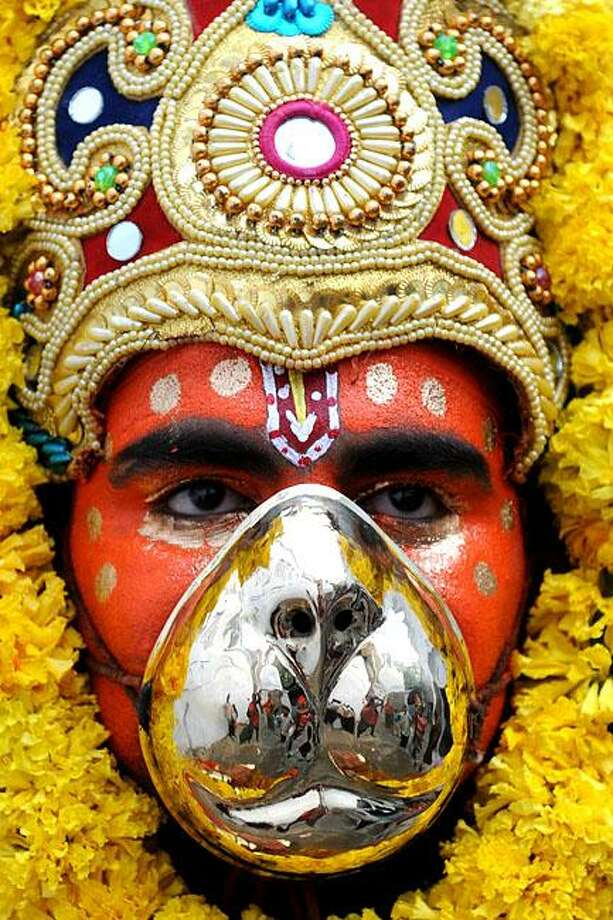 Monkey shine:A silver-snouted Hindu devotee representing the monkey god Hanuman marches in a religious procession celebrating the festival of Dussehra at the Durgiana Temple in Amritsar, India. Dussehra symbolizes the victory of good over evil in Hindu mythology. Photo: Narinder Nanu, AFP / Getty Images / AFP / Getty Images