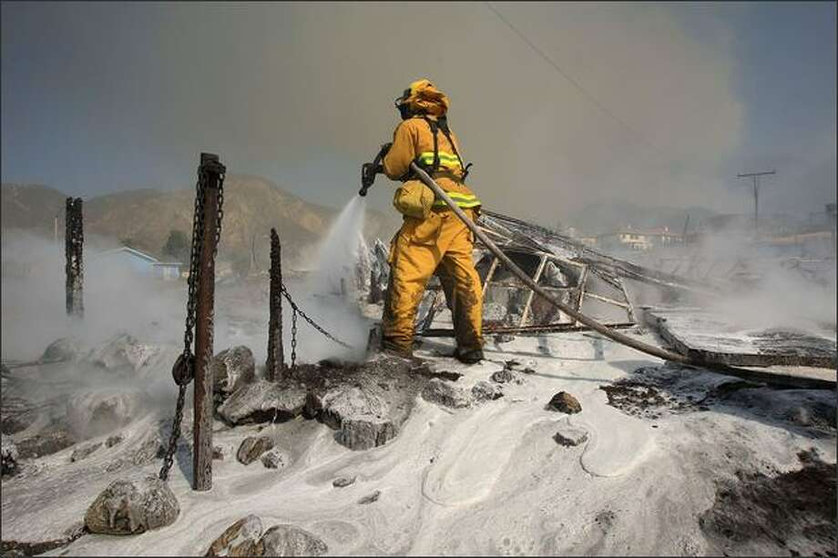 Firefighters douse the smoldering remains of a structure that burned in the Merek fire on Monday near the Los Angeles area community of San Fernando, California. The Merek fire is being fuel by erratic winds that have been gusting to 75-miles-per-hour along the fireline in first Santa Ana Wind event of the season. Photo: Getty Images / Getty Images