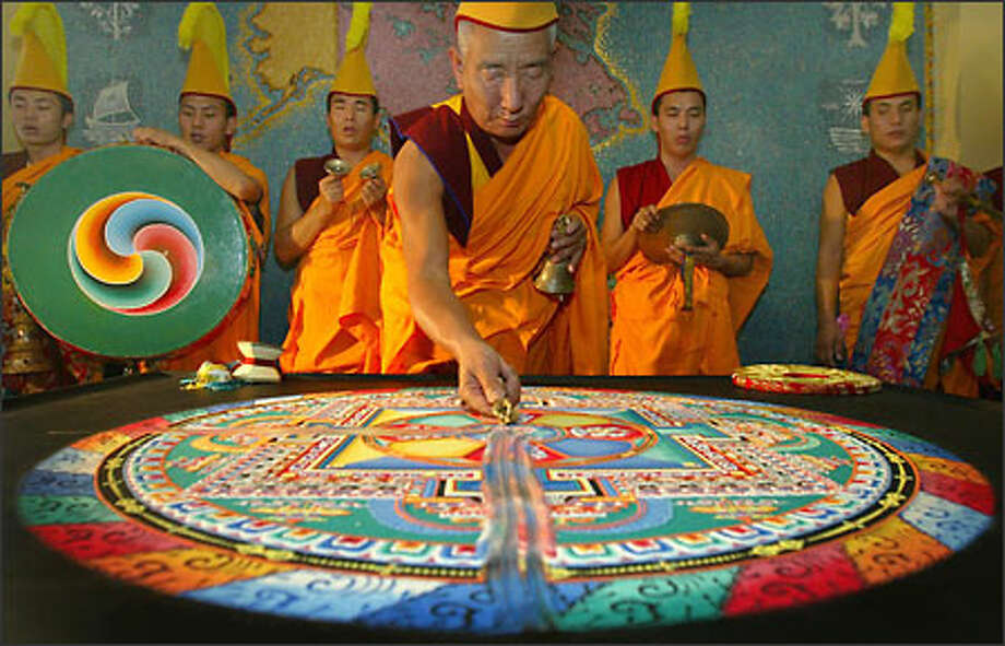 Tibetan monk Geshi Tsultrim Gyatso dismantles a mandala, an ornate work made with colored sand, at Bastyr University in Kenmore. The monks worked on the elaborate creation from Monday morning until it was destroyed Tuesday afternoon.  The ceremony symbolizes the impermanence of everything. Photo: Joshua Trujillo, Seattlepi.com / seattlepi.com