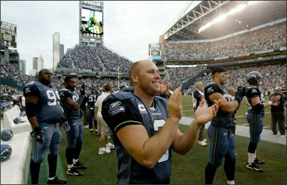 Josh Brown and many of the other Seattle Seahawks applaud as Mack Strong raises the 12th Man flag before the start of the game Sunday night.  An injury forced Strong to retire last week after 15 years of football. Photo: Scott Eklund, Seattle Post-Intelligencer / Seattle Post-Intelligencer