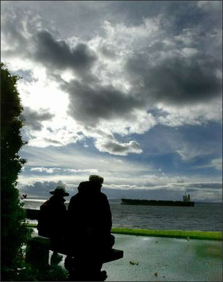 Nancy and Larry Rudolph pause to rest and enjoy a sun break in the clouds while taking in the view of Puget Sound from the west end of the Elliott Bay Marina. Photo: Grant M. Haller, Seattle Post-Intelligencer / Seattle Post-Intelligencer