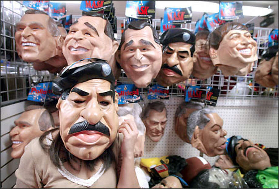Trying to find the perfect Halloween costume, Kim Trujillo of Everett tries on a Saddam Hussein mask at Champion Party Supply in Seattle yesterday while surrounded by the likenesses of other world power brokers such as President Bush, Secretary of State Colin Powell and Microsoft Corp. founder Bill Gates. [NOTE: An earlier version of this caption misnamed the store.] Photo: Joshua Trujillo, Seattlepi.com / seattlepi.com