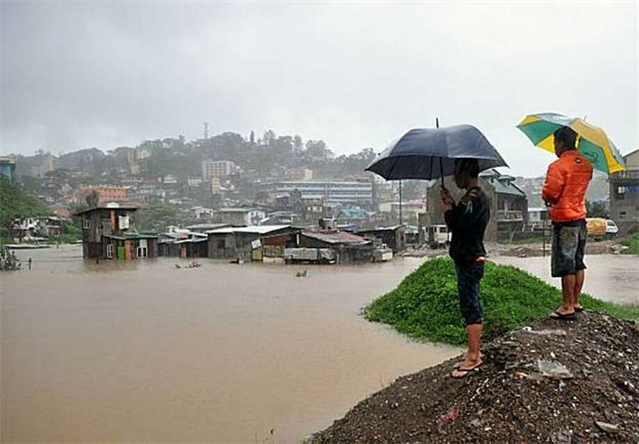 Submerged shantytown:Filipinos survey their flooded homes as rain continues to pour in Baguio City. Typhoon Megi, the strongest typhoon to hit the Philippines in years, killed at least 10 people and destroyed vital rice fields. Photo: Ted Aljibe, AFP / Getty Images / AFP / Getty Images