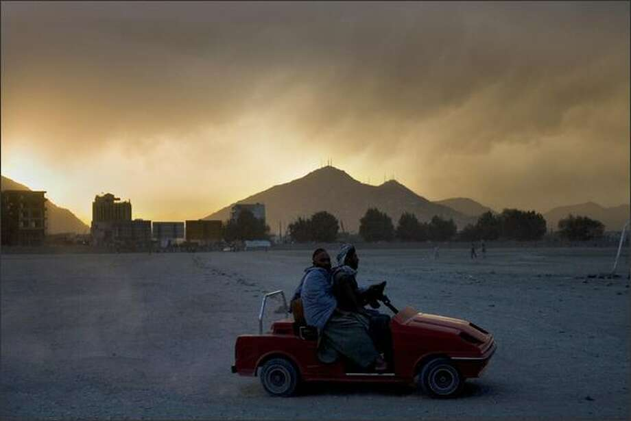Afghan men enjoy a joyride on a toy car at dusk in Kabul on Tuesday. Photo: Getty Images / Getty Images