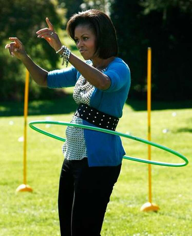U.S. first lady Michelle Obama hula hoops on the South Lawn of the White House during an event promoting exercise and healthy eating for children, Wednesday, in Washington, DC. The Healthy Kids Fair included events on cooking healthy meals and emphasized children getting a proper amount of outdoor exercise each day. Photo: Getty Images / Getty Images