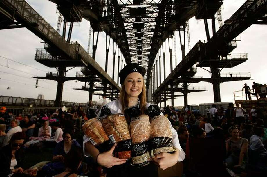 "A women poses while handing out bread during a picnic breakfast on the Sydney Harbour Bridge on Sunday in Sydney, Australia. For the first time in its history, Australia's iconic Sydney Harbour Bridge will be closed to commuter traffic to host 6,000 people for the ultimate picnic breakfast. This unique production, dubbed ""Breakfast on the Bridge,"" is a brand new event introduced as part of Crave Sydney, a new celebration of Sydney's unmatched way of life with 31 days of food, outdoor art and fun during the month of October. Photo: Getty Images / Getty Images"