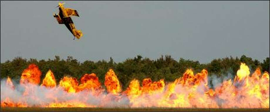 A plane flown by Jim LeRoy, of the Tenstix of Dynamitye team of LeRoy and Jurgis Kairys, flies over explosions during a performance Friday on the first day of the 2006 Naval Station Jacksonville Air Show in Jacksonville, Fla. (AP Photo/The Florida Times-Union, Don Burk)