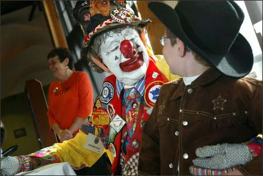 """I love you,"" Johnny Pownall, age 5, from North Bend, tells J.P. Patches at the Seattle Aquarium on Sunday.  The former children's TV host, played by Chris Wedes, 79, signed autographs and greeted the public for more than two hours as children went trick-or-treating at businesses along the waterfront.  This was one of J.P.'s rare public appearances since Wedes was recently diagnosed with blood cancer. Photo: Karen Ducey, Seattle Post-Intelligencer / Seattle Post-Intelligencer"
