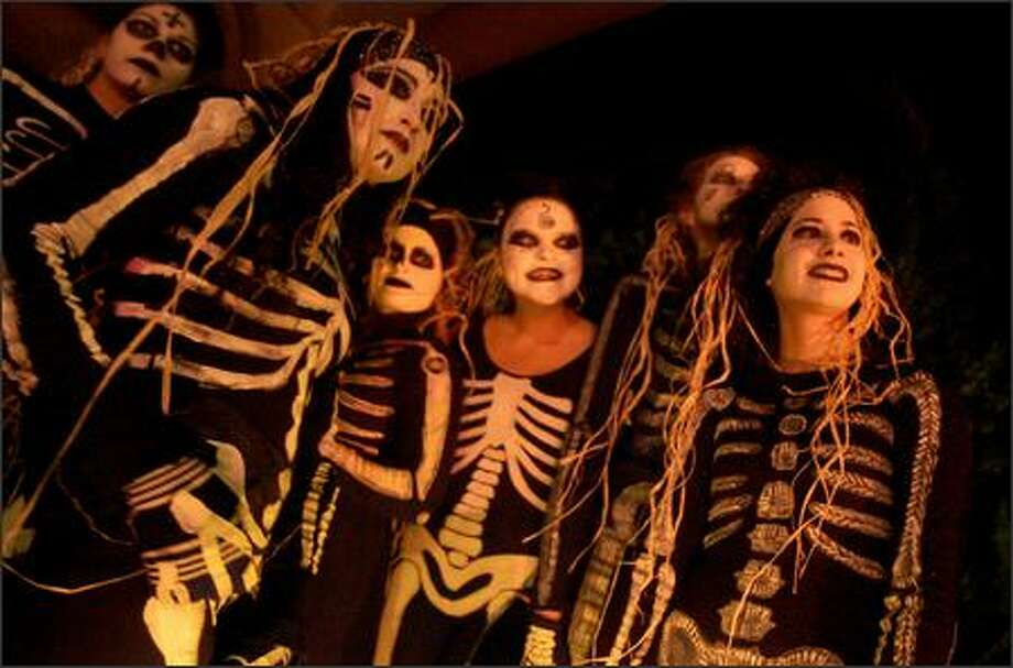 Dancers with VamoLà, a Brazilian drum and dance ensemble based in Seattle, stand near a space heater as they wait to perform at Troll o'ween, a Fremont Halloween celebration sponsored by the Fremont Arts Council, under the Aurora Bridge by the Fremont Troll Tuesday night, October 31, 2006. Photo: Mike Kane, Seattle Post-Intelligencer / Seattle Post-Intelligencer