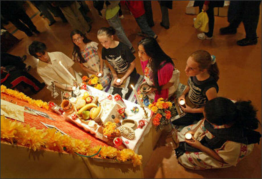 Rainier Valley Youth Theater members, clockwise from left, Bob Goodin, 14; Rebecca Mostow, 13; Liz Parker, 14; Luz Garcia, 16; Amelia Holmes, 12; and Celia Garcia, 12, pray at a Dia De Los Muertos altar during a Day of the Dead celebration at El Centro de la Raza on Beacon Hill. The altars made by community groups and volunteers wil be on display until Nov. 23. They feature food and drink offerings to deceased family members. Photo: Joshua Trujillo, Seattlepi.com / Seattle Post-Intelligencer