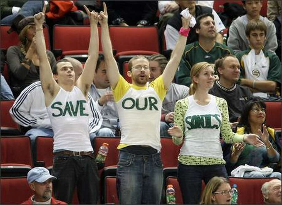 These Seattle Sonics fans at Wednesday night's season opener at KeyArena are unamious that they want their team to stay in town. Photo: Mike Urban, Seattle Post-Intelligencer / Seattle Post-Intelligencer