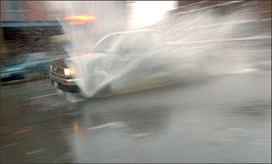 Standing water at Third and Bell in downtown Seattle caught motorists by surprise as heavy rain pelted the city on Election Day. Photo: Jeff Larsen, Seattle Post-Intelligencer / Seattle Post-Intelligencer
