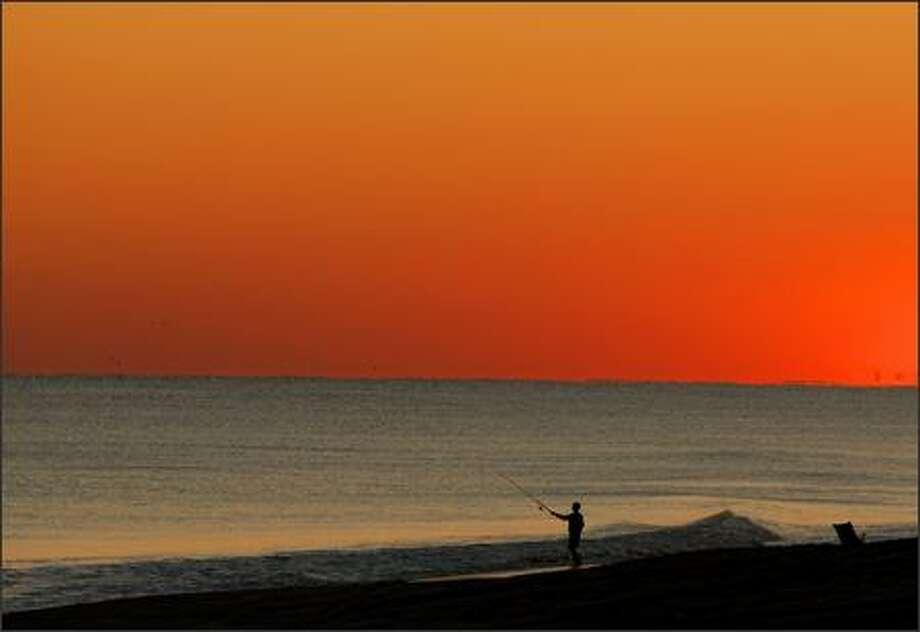 In this photo released by East Carolina University, Steven Smith enjoys fishing on the beach in Emerald Isle, N.C., Friday. (AP Photo/East Carolina University, Marc J. Kawanishi)