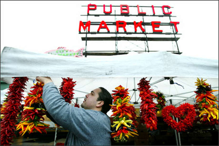 Robert Nunez prepares a colorful display of hot peppers from Alvarez Farms at Pike Place Market recently. The Mabton farm grows 80 varieties of peppers. Photo: Paul Joseph Brown, Seattle Post-Intelligencer / Seattle Post-Intelligencer