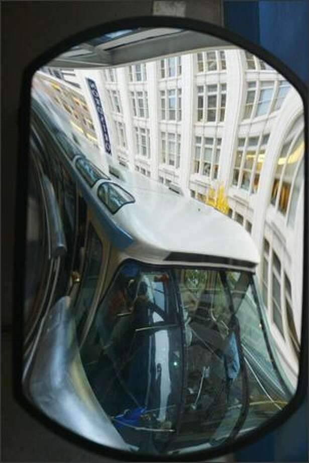 A mirror reflection shows the Seattle Monorail's blue train pulls into Westlake Center. The popular tourist attraction is back in service and is free to riders through Sunday. It runs between the Seattle Center and Westlake Center from 11 a.m. to 7 p.m. Photo: Meryl Schenker, Seattle Post-Intelligencer / Seattle Post-Intelligencer