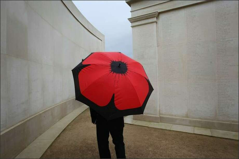 A mourner carries an umbrella imprinted with a poppy as he takes part in the Remembrance Day Service marking the 90th anniversary since the end of World War I at the Armed Forces Memorial at The National Arboretum on Sunday near Lichfield, England. Photo: Getty Images / Getty Images