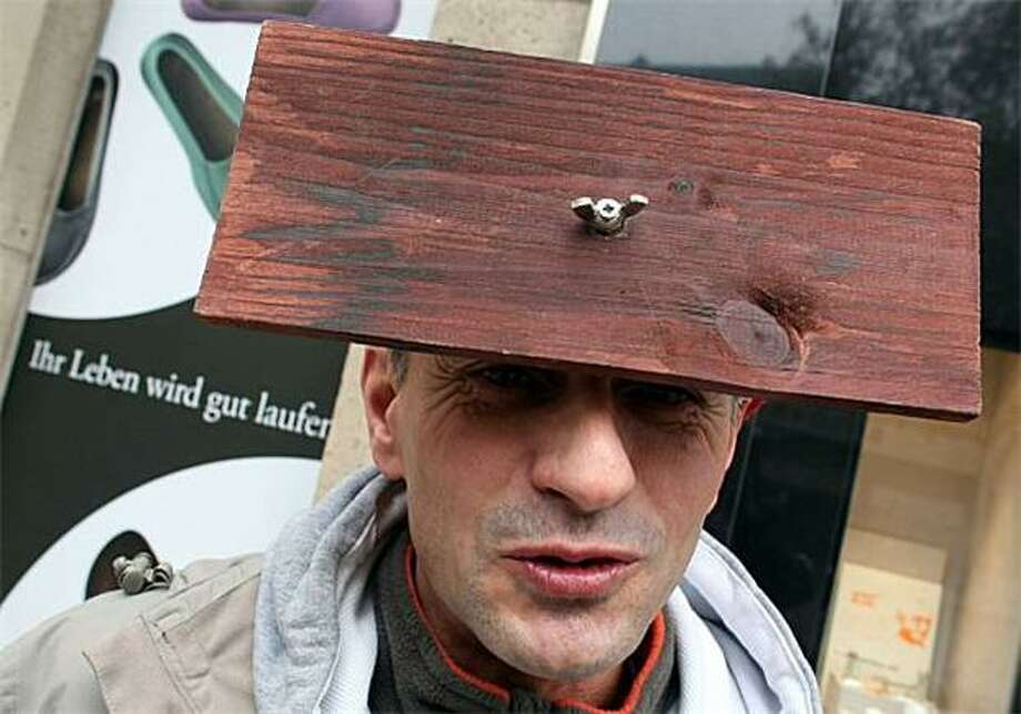 Wingnuts come out of the woodwork for carnival:A man with a board apparently screwed onto his forehead celebrates the beginning of carnival season in Cologne, Germany. Photo: Oliver Berg, AFP / Getty Images / AFP / Getty Images