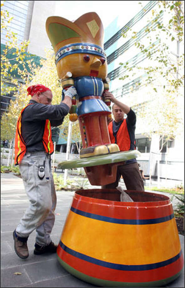 Jack Ryder, left, and Dylan Davalle install a 6-foot-tall nutcracker named Kingston in front of Seattle's Federal Courthouse, where it will stay until after the new year. Created by Bruce and Shannon Anderson, Kingston is one of 40 artist-made nutcrackers that have been placed downtown as part of the Nutcracker March, a fund-raiser for Seattle's Northwest Center. Another 10 have been saved for Macy's Thanksgiving Day parade. All the works are being auctioned online at NutcrackerMarch.com. Photo: Meryl Schenker, Seattle Post-Intelligencer / Seattle Post-Intelligencer