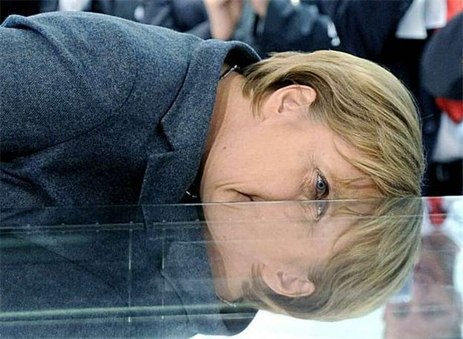 Oh no, they've invented a politician cloner! German Chancellor Angela Merkel inspects a cloud chamber which makes visible radiation as she tours the Medica World Forum for Medicine in Duesseldorf. Photo: Julian Stratenschulte, AFP / Getty Images / AFP / Getty Images