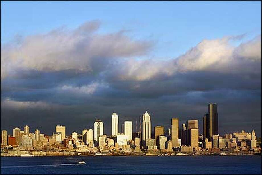 Downtown Seattle is illuminated at sunset as wind-swept clouds provide a dramatic backdrop. Photo: Karen Ducey, Seattle Post-Intelligencer / Seattle Post-Intelligencer