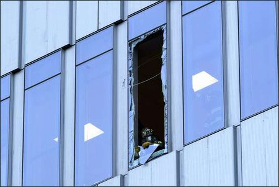 A firefighter removes glass from a window of the WAMU SAM building downtown in Seattle on Monday. Construction workers lost control of a replacement panel due to strong winds and the panel shattered the glass. Because of glass in the street and the danger of more falling, traffic at the corner of 1st Ave and Union was held up for hours. No one was hurt. Photo: Karen Ducey, Seattle Post-Intelligencer / Seattle Post-Intelligencer