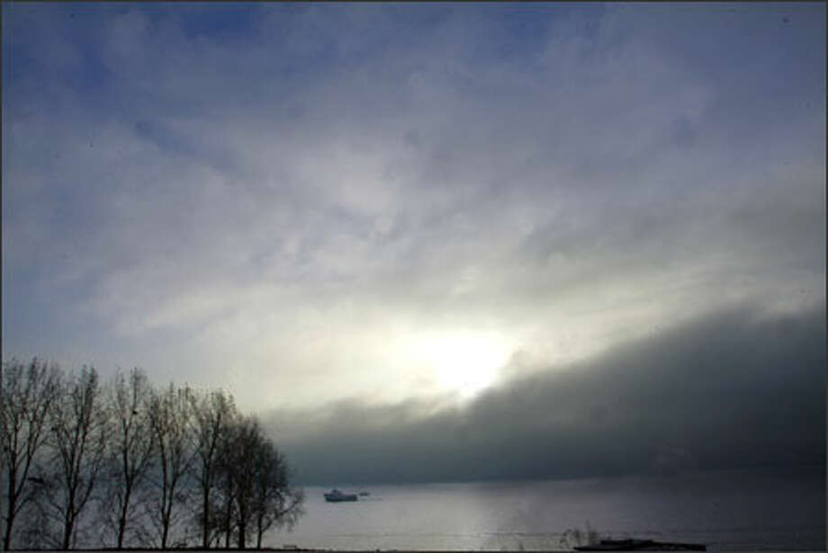 Fog crosses Seattle's Elliott Bay as the sun tries to break through on Monday afternoon. Photo: Karen Ducey, Seattle Post-Intelligencer / Seattle Post-Intelligencer
