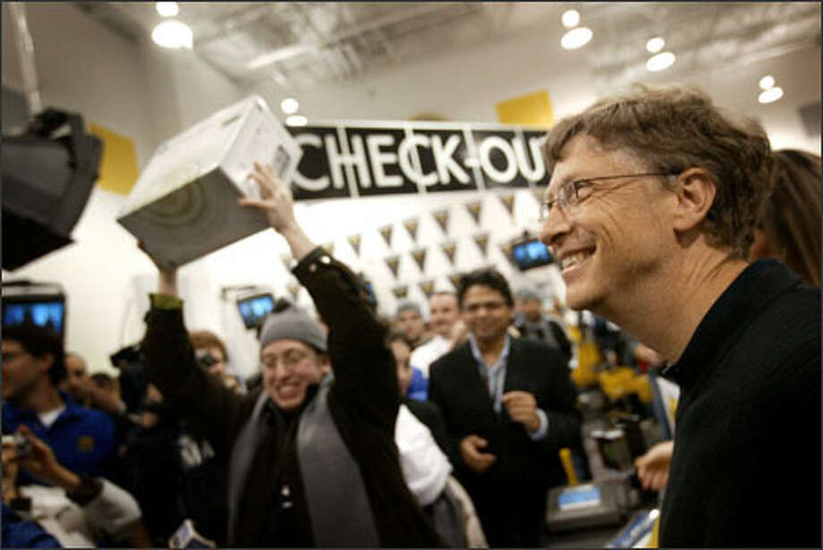 Microsoft Chairman Bill Gates is all smiles as Dan Friedman, 26, holds up the first Xbox 360 sold near midnight Monday at the Best Buy on 120th Avenue Northeast in Bellevue. Hundreds of enthusiasts waited in line to snare one of the consoles. Photo: Joshua Trujillo, Seattlepi.com / Seattle Post-Intelligencer