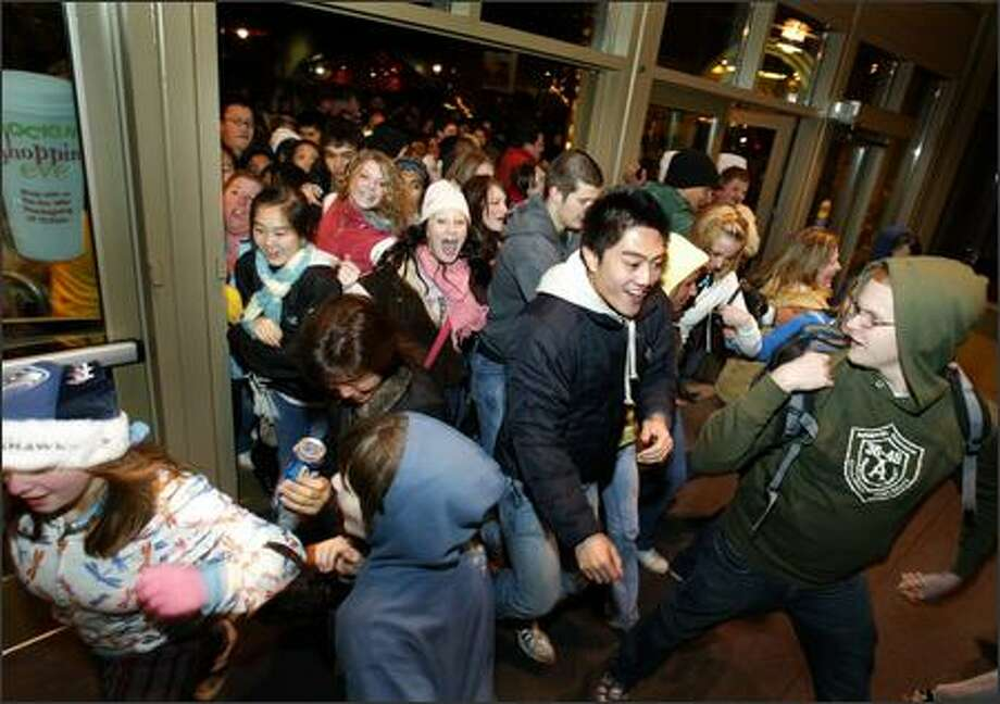 "Customers burst through the doors as Alderwood Mall opens at 12:01 a.m. the day after Thanksgiving for ""Black Friday"" sales. Photo: Joshua Trujillo, Seattlepi.com / seattlepi.com"