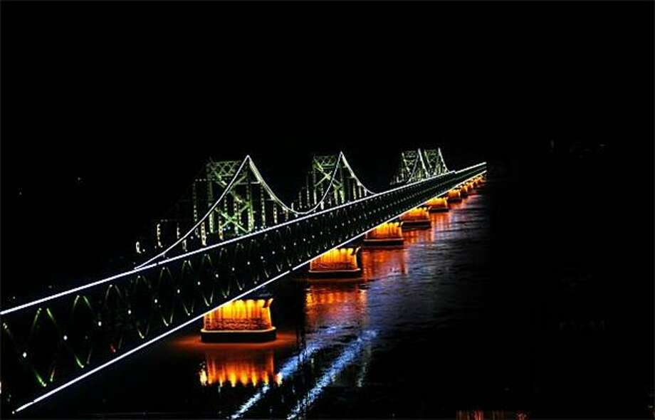 It goes nowhere in style:Lights decorate a bridge in Dandong, China, that ends in the middle of the the Yalu River separating North Korea and China. The span was bombed by the United States in 1950 during the Korean War. Photo: Frederic J. Brown, AFP / Getty Images / AFP / Getty Images