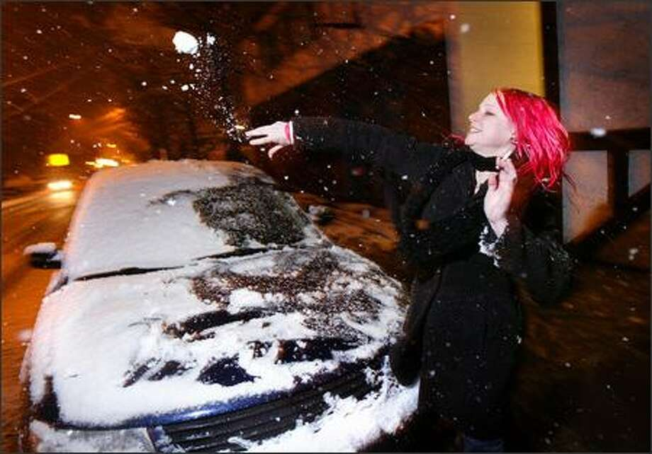 Stephanie Dailey, who works at Dante's, a bar in the University District, lobs a snowball at friends at The Monkey, another bar across the street, as the snow fell on Seattle Sunday night. Photo: Joshua Trujillo, Seattlepi.com / seattlepi.com