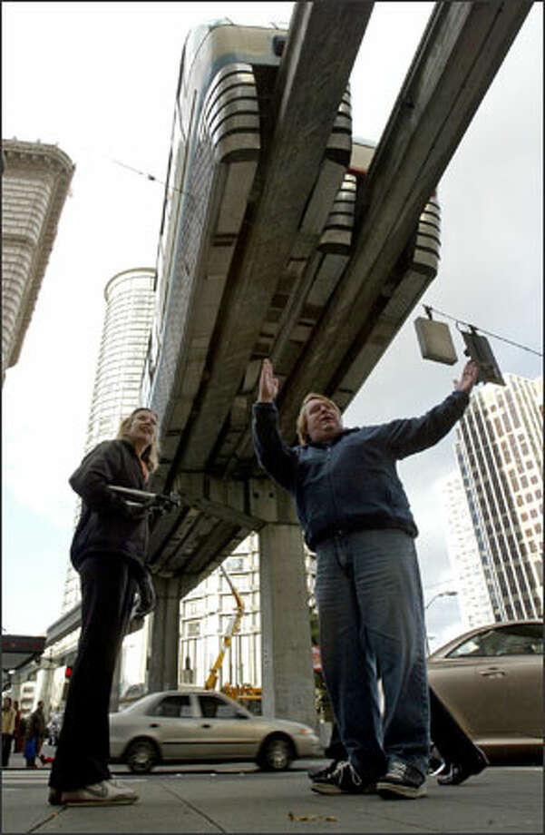 Metro driver Mark Peterson explains to Brigitte Steinheider of Tulsa, Okla., how the Monorail trains hit each other Saturday. No one was seriously injured in the first-of-its-kind accident for the system. Photo: Mike Urban, Seattle Post-Intelligencer / Seattle Post-Intelligencer