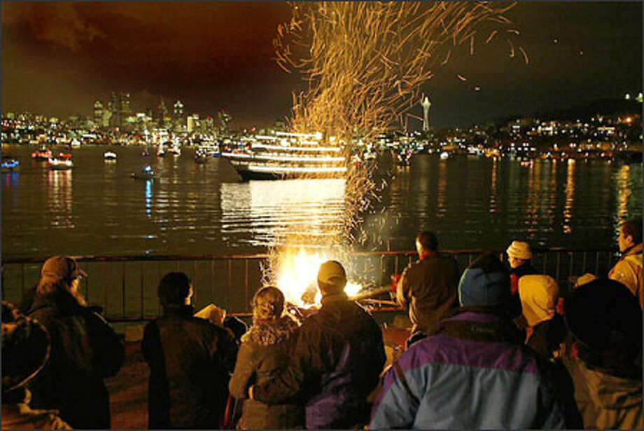 The bonfire crackles while people gather at Gas Works Park for the first night of the Argosy Christmas Ship Festival. The Spirit of Seattle, decorated with thousands of lights, each night leads the holiday flotilla to different locations where people onshore gather to hear the carolers on the ships. Photo: Meryl Schenker, Seattle Post-Intelligencer / Seattle Post-Intelligencer