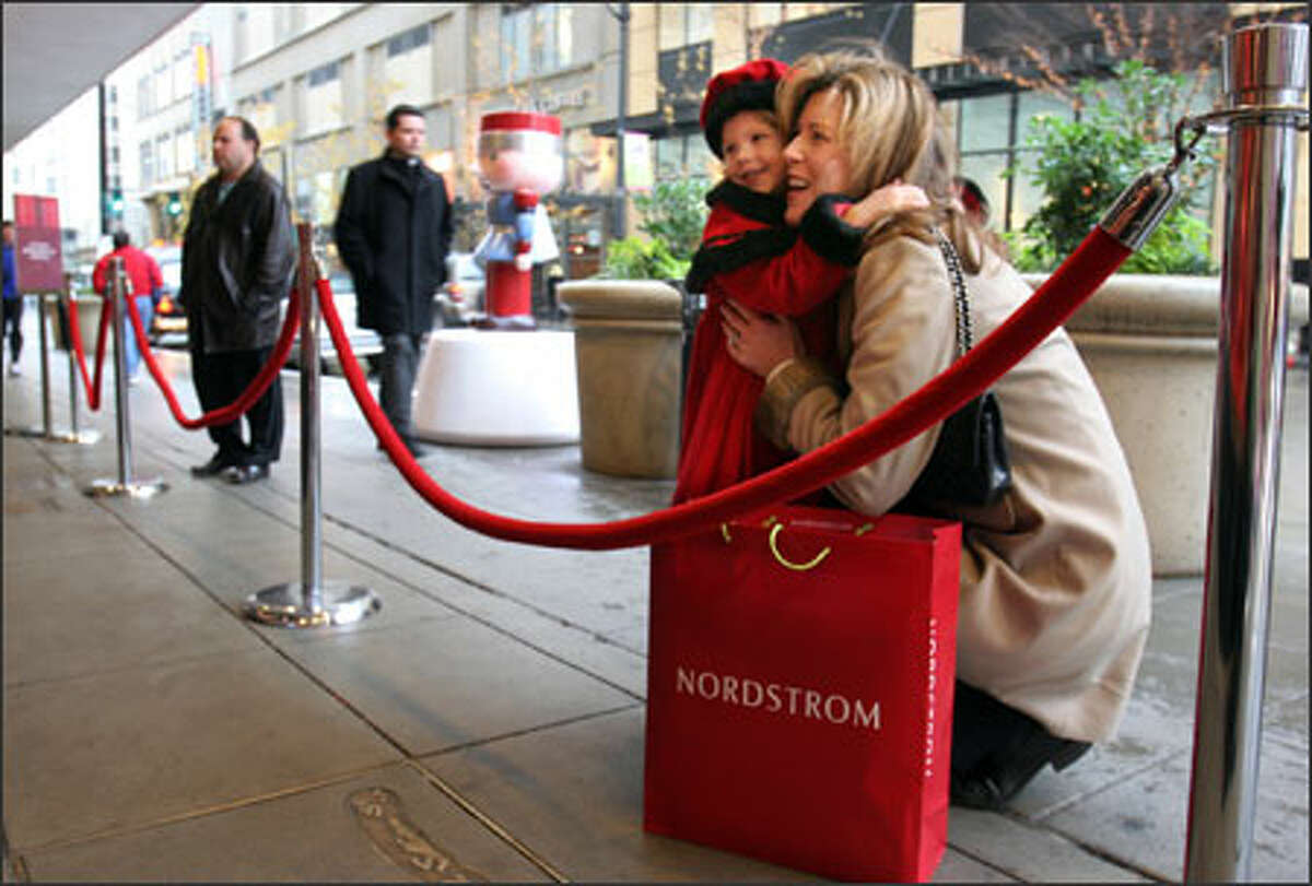 BEFORE: Karen Ombrellaro and daughter Isabella, 5, of Bothell smile at the Santa inside the downtown Seattle Nordstrom.