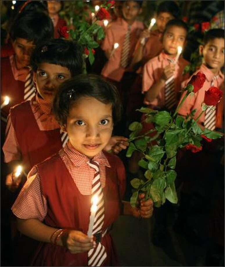 Indian Schoolchildren hold flowers and candles in memory of those killed in the Mumbai attacks in Mumbai, on Monday. Photo: Getty Images / Getty Images