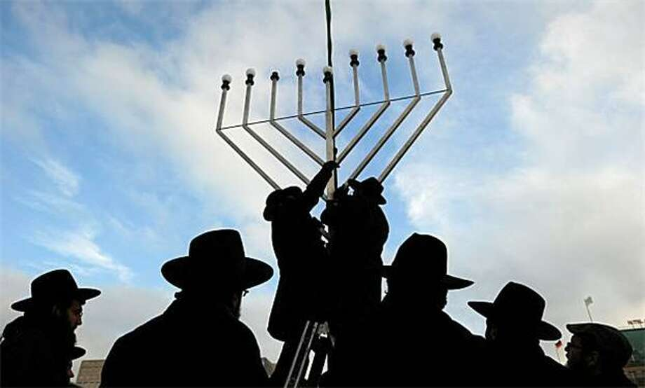 Rabbis erect an oversized Menorah in front of Berlin's Brandenburg Gate ahead of the eight-day-long Hanukkah, or Festival of Lights, celebration marking the rebellion of Maccabee Jews against the Greeks in 165 BC. Photo: Johannes Eisele, AFP / Getty Images / AFP / Getty Images