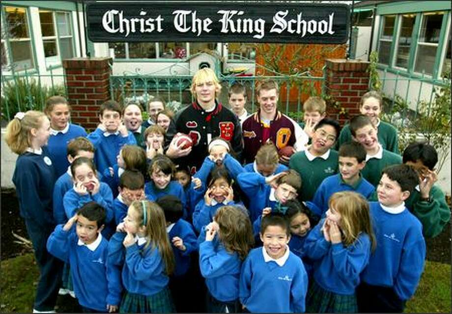 "Christ the King students show off their ""funny"" faces after having their photo made with quarterbacks Cole Morgan from Ballard, left, and Joey Shanks of O'Dea. Morgan and Shanks attended the school when they were younger; now both are headed to state championship football games. Photo: Grant M. Haller, Seattle Post-Intelligencer / Seattle Post-Intelligencer"