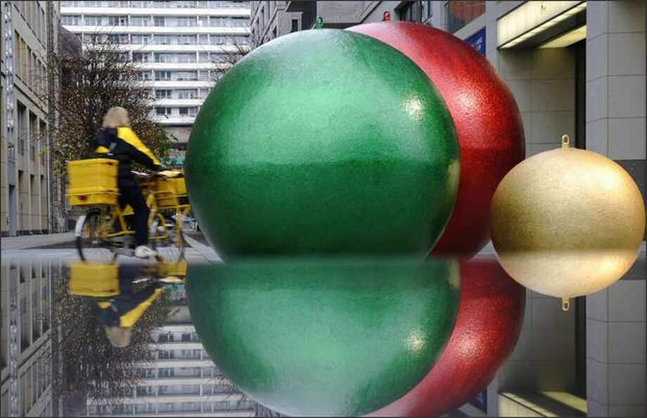 A postwoman rides her bike past three huge spheres, installed as Chrismas decoration on Tuesday in Berlin. Photo: Getty Images / Getty Images