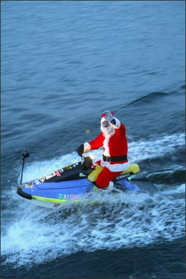 Santa waves to passengers on the Virginia V from a Jet Ski as he rides alongside the Special People's Holiday Cruise on Lake Washington. More than 2,500 developmentally disabled adults boarded 300 boats around the Puget Sound area to take part. Photo: Grant M. Haller, Seattle Post-Intelligencer / Seattle Post-Intelligencer