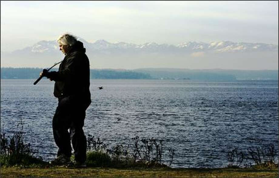 With a fish on the end of his line, fisherman Larry Johnson looks for a spot where he can easily net his catch. Photo: Gilbert W. Arias, Seattle Post-Intelligencer / Seattle Post-Intelligencer