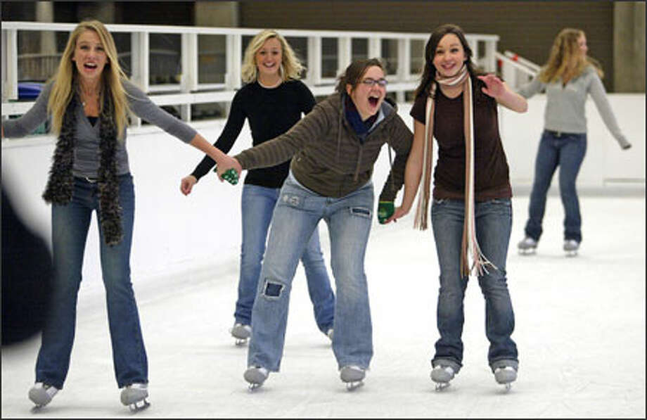 Members of the Bothell High School Jazz Choir have some fun together while attempting to also stay upright at the Seattle Center Winterfest Ice Rink on Wednesday. They were killing time before a caroling gig at the top of the Space Needle. Stacy Olen, left, and Amanda Westby, right, assist Molly Sopher on the ice. Photo: Mike Urban, Seattle Post-Intelligencer / Seattle Post-Intelligencer