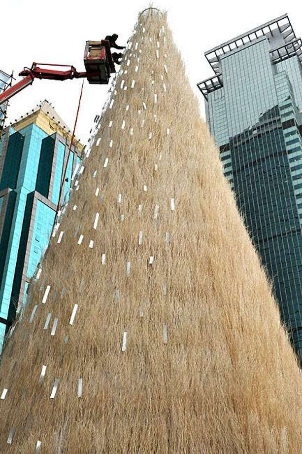 Nothing says Christmas like a giant fur tree: At a Shanghai mall, workers trim a giant shag carpet cone with shopping receipts. Or possibly scraps of ribbons. Photo: Philippe Lopez, AFP / Getty Images / AFP / Getty Images
